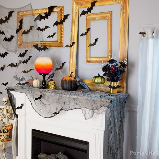 Paper bats and paper gold frames over mantel
